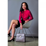 british luxury womenswear woman wearing red top and black skirt sat on a white chair with legs crossed holding a handbag