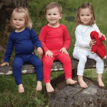 three toddlers wearing superlove merino childrens clothes sat on a bench