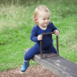 superlove childrenswear blue outfit boy on a see saw