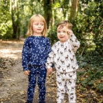 boy and girl wearing twinkledust childrens pyjama sets in woods