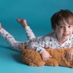 british childrenswear category image showing boy wearing twinkle dust pyjamas on floor with teddybear
