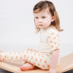 girl wearing clothes by british babies sat on wood
