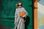 category image showing a woman in long grey coat holding a sarah haran brown handbag under her arm