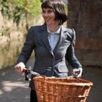 british made bikes category image showing a woman holding a bicycle with a basket on the front