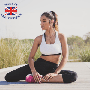 best british athleisure and activewear brands, british blog, made in britain, woman in activewear stretching on the ground, white crop top and black bottoms