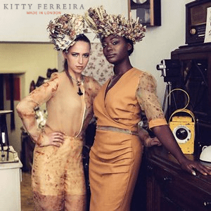 two women models in designer british african style dress with elaborate headwear in vintage uk style setting one black woman one white woman with clothes designed by kitty ferreira made in london