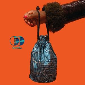 ola ola, black womans arm holding a handbag blue deigned bag with string handle on orange background, made in uk