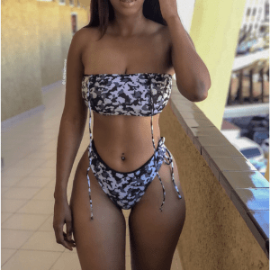 lajoi swimwear, close up of black mixed race woman in patterned swim bikini top and bottoms walking beside a pool wearing uk handmade swimwear
