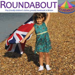 roundabout childrens clothing, little girl wearing a dress holding a union jack british flag staing on a pebble beach, british made children's clothes, kidswear made in uk
