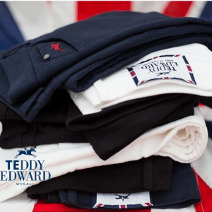 teddy edward luxury clothing, pile of men's polo shirts moleskin jeans next to a british flag by teddy edward, british made men's clothing