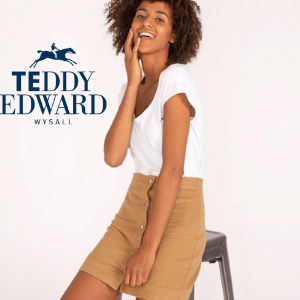 mixed race woman in white t shirt and cord skirt sat on a stool wearing teddy edward clothing made in britain, british made women's clothes
