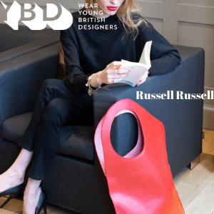 russell russell, british handbag designer, woman sat of sofa with large red designer handbag by russell russell young british designers