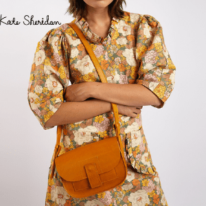 kate sheridan, woman with brown handbag made by kate sheridan and made in england, handbag designers