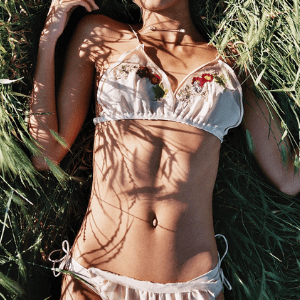 crease lingerie brand woman in embroidered triangle bra bralett laid on grass made in Britain, underwear for ladies