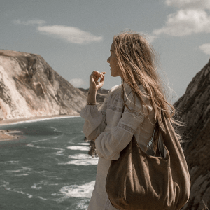 woman on a cliff with sea view holding a zephyr vegan dust bag hand bag in brown made in England