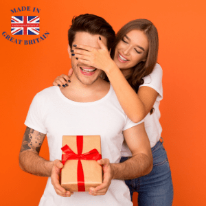 british gifts for him, Christmas gift ideas for men, made in great britain, women giving a present to a man with tattoos while covering his eyes