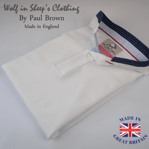 a folded white men's polo shirt with navy collar by wolf in sheeps clothing brand, british polo shirt brands,