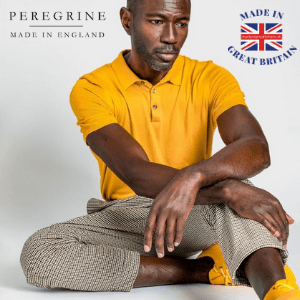 black man sat on floor wearing a bright yellow men's polo shirt by peregrine clothing made in uk