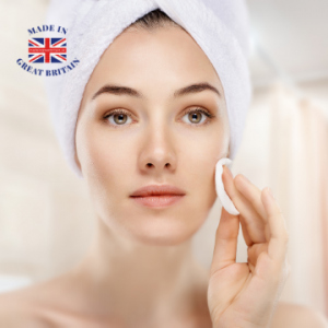woman applying face cream while sitting on her bed with a towel wrapped round her head, british beauty and skincare, british business directory, uk made