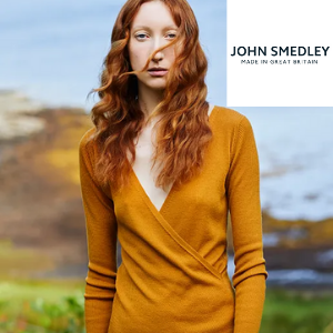 woman with curly ginger hair wearing an orage cross over john smedley fine knitwear top, women's clothes made in britain