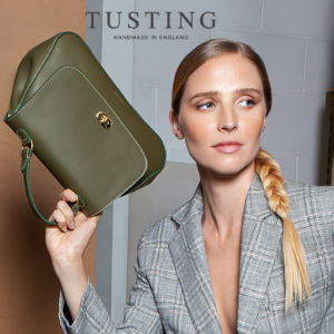 woman holding a green tusting made in england small handbag, uk made handbag brands