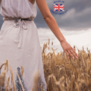 british made women's clothes, woman walking through british field of corn with cloudy sky