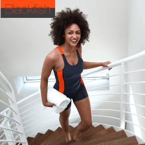 black woman walking upstairs in swimwear tankini holdiung a white towel, blackfish swimwear all in one tankini