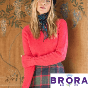 brora cashmere jumper worn by a woman in tartan skirt, brara cashmere made in scotland