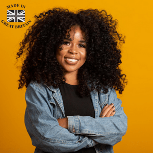 black owned british made, uk black owned businesses, black business woman with afro hair smiling in casual denim shirt next to a black and white union jack british flag, buy british campaign