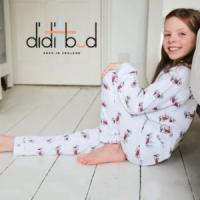 didi and bud, british made kids sleepwear, little girl in onesie sat on floor smiling next to her bed,