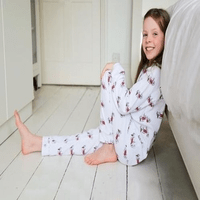 british childrens clothing category image showing a girl sat on floor in pyjamas