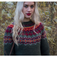 top half of a woman with blonde hair wearing a knitted jumper, made in britain