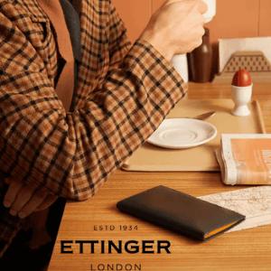 ettinger luxury wallets, man in luxury jacket sitting at table drinking tea with ettinger wallet